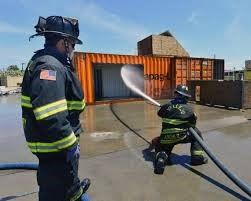 Firefighter training with fire hose spraying structure